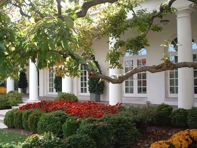 Photo of White House Rose Garden with the Oval Office in the background.