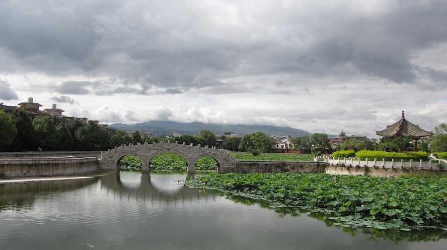 photo of stone bridge over water with mountains in the background