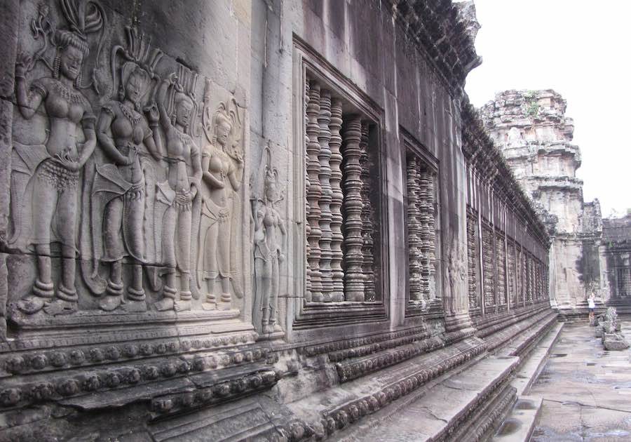 Stone wall inside Angkor Wat with relief figures and decorative windows