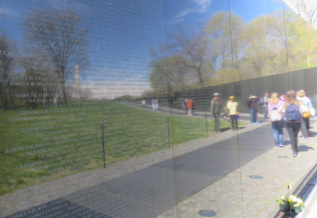 Vietnam War Memorial reflecting visitors, trees and the Washington Monument