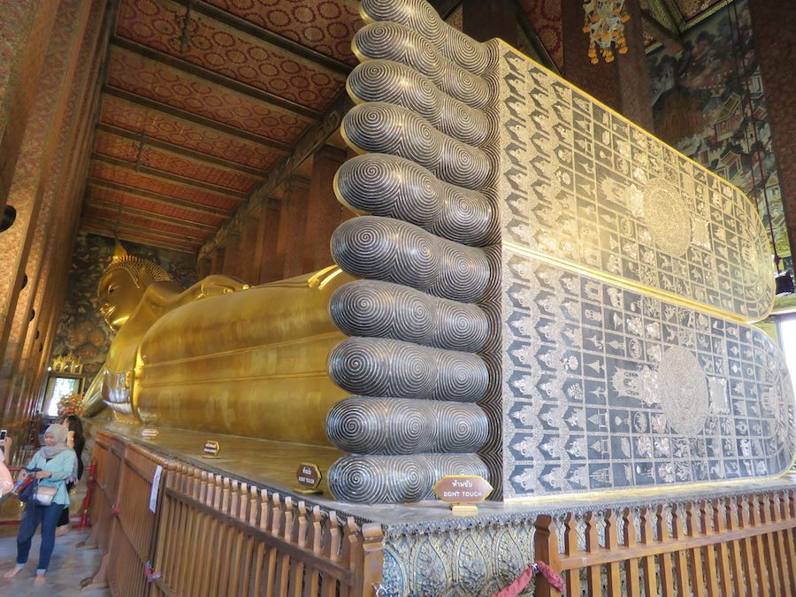 large reclining Buddha (in gold) with inscriptions on large feet
