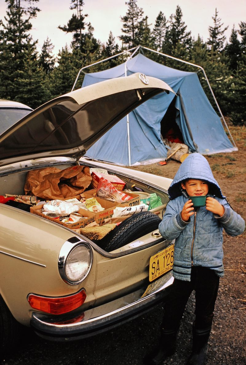VW with front trunk open and kid in front of a blue tent